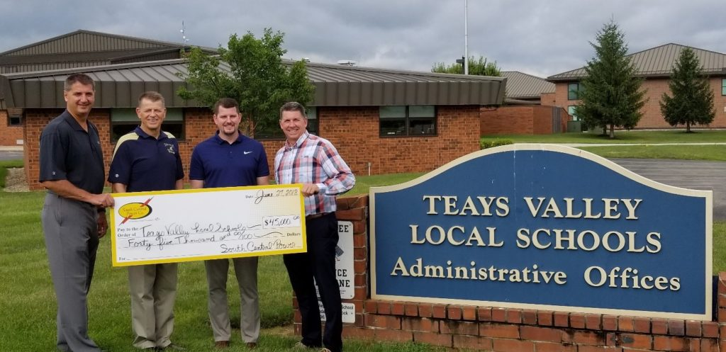 From left, Stacy Overly, treasurer, and Robin Halley, superintendent of the Teays Valley Local School District, accept a $45,000 lighting rebate check from Kyle Heavrin, key accounts manager, and Jeff Campbell, community development manager.